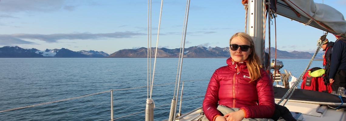 Serenity Explorers cestování a dovolená| Mindfullness a Duševní zdraví - Ostrov Špicberky v Arktidě, Severní ledový oceán. Žena klidně sedící na přídi lodě se dívá do západu slunce.